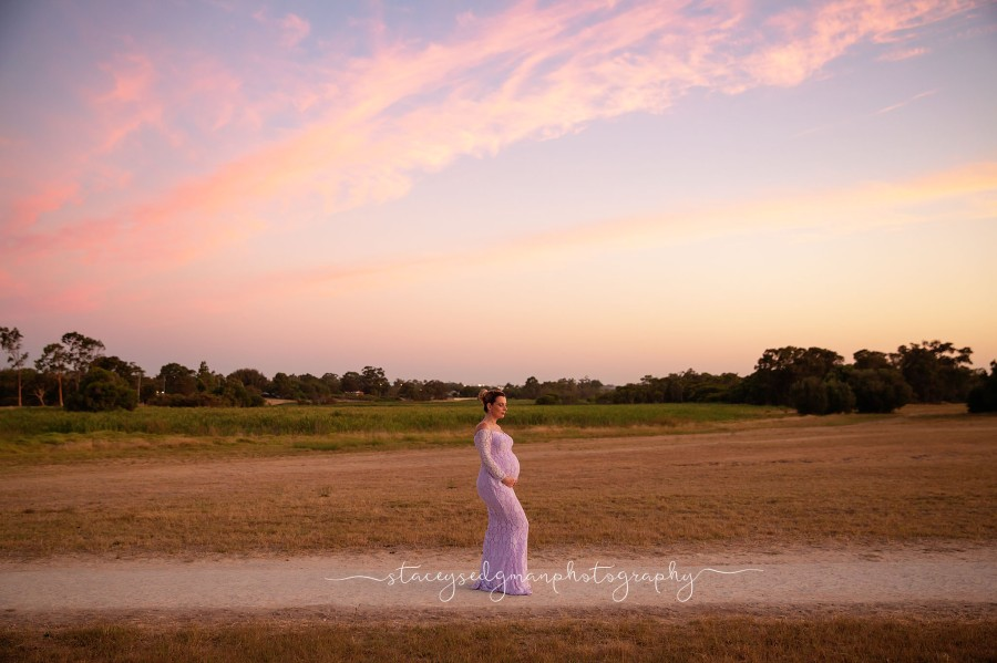 Landscape maternity photograph of woman in eden elizabeth gown at sunset