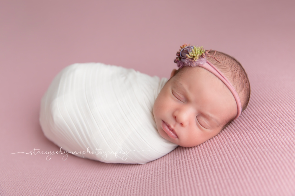 Baby girl posed on a pink fabric drop wearing an ivy and nell headband