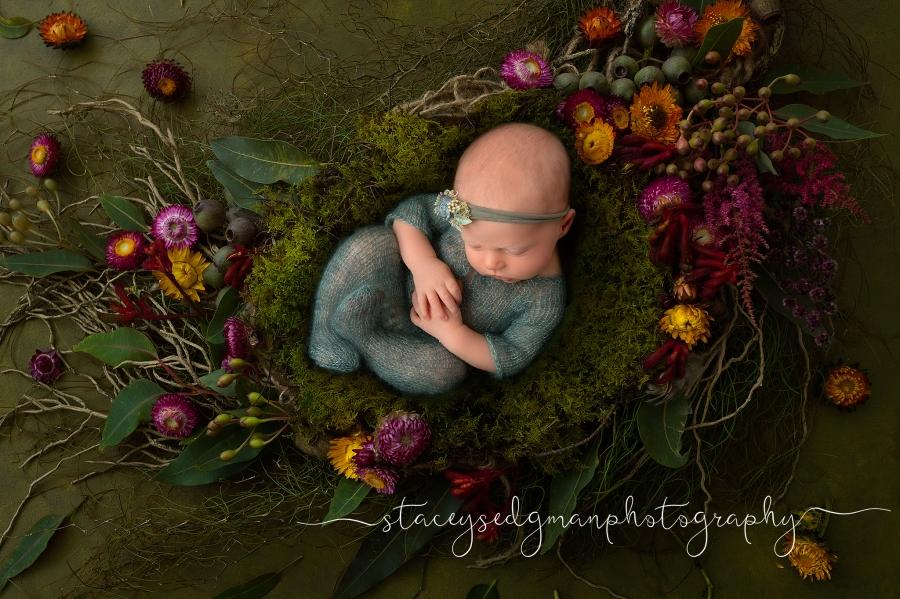 Newborn girl in green footed romper on green floral luisa dunn digital nackground