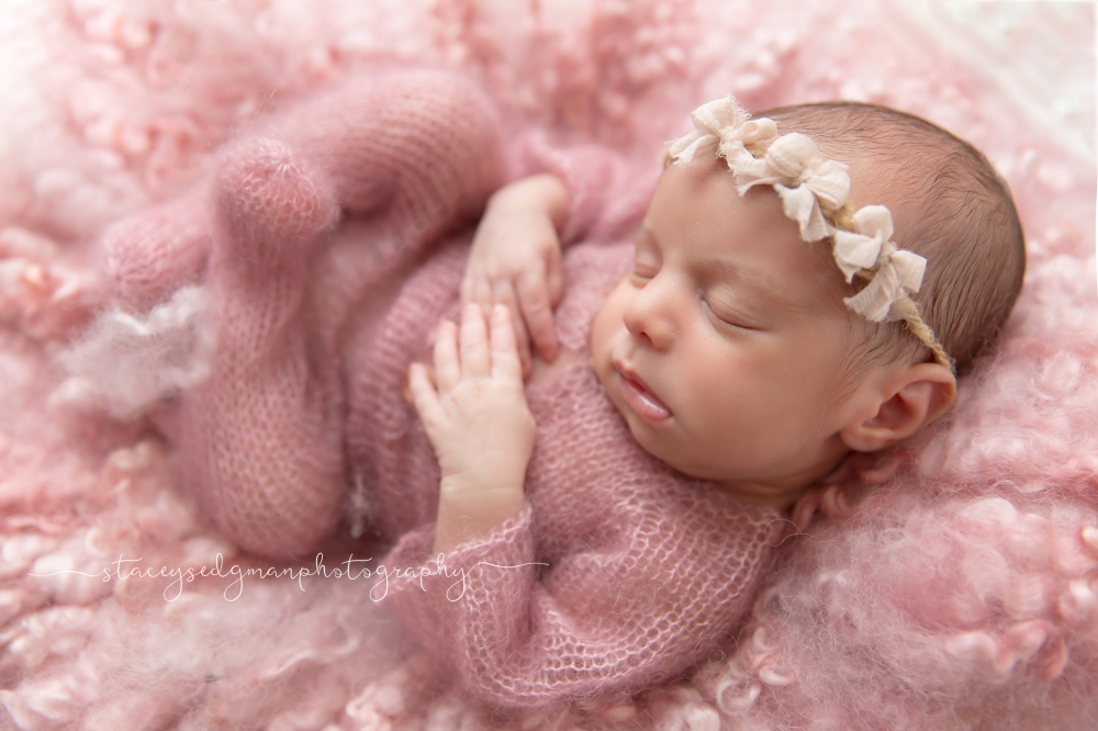 Baby posed in pink knitted romper on pink curly felt and backlit