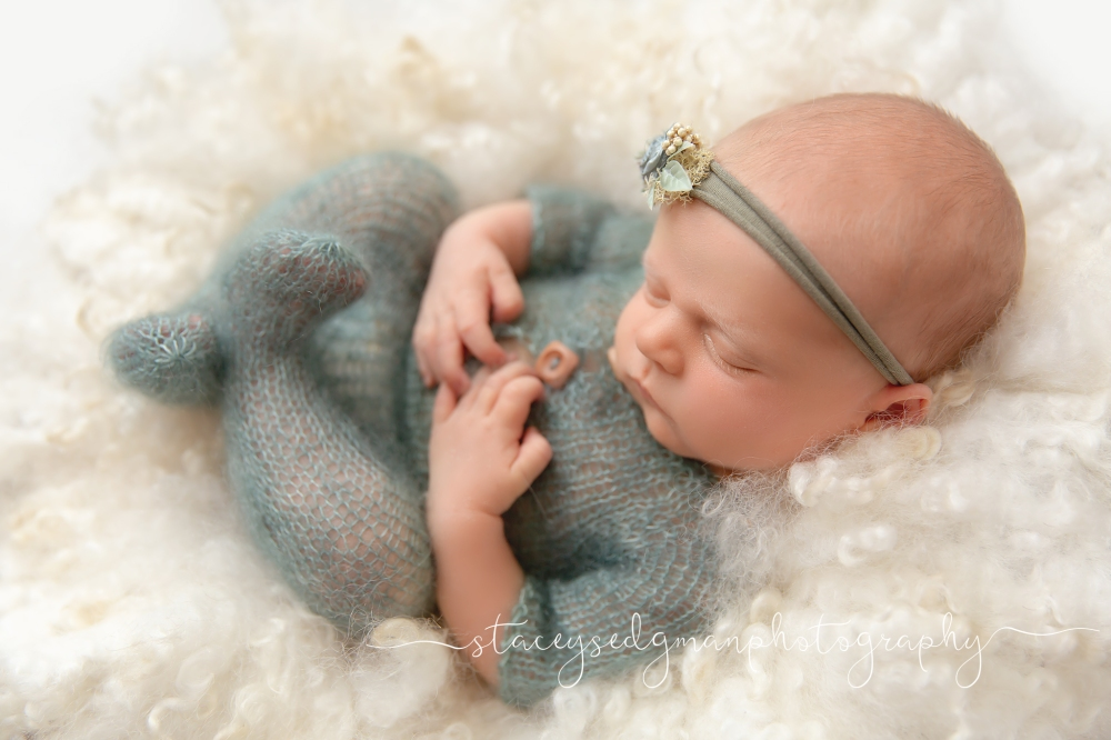 newborn girl in green knitted footed romper on cream curly felt