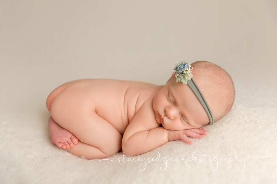 newborn girl in tushy up pose on cream fuzzy fabric from shooting stars prop shop