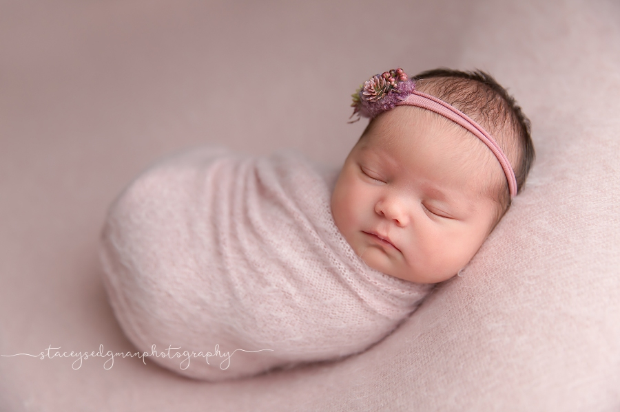 Baby girl wrapped in pink on a pink backdrop
