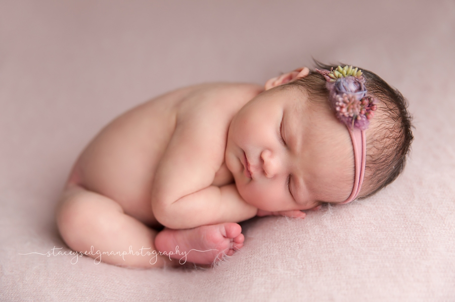 newborn girl in taco pose on pink backdrop