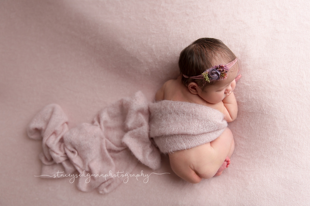 newborn girl in bum up pose on pink backdrop