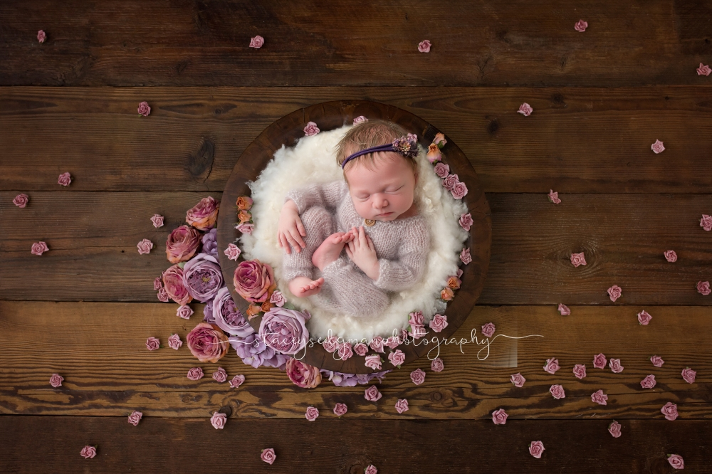 Baby in a bowl surrounded by flowers on a wooden backdrop