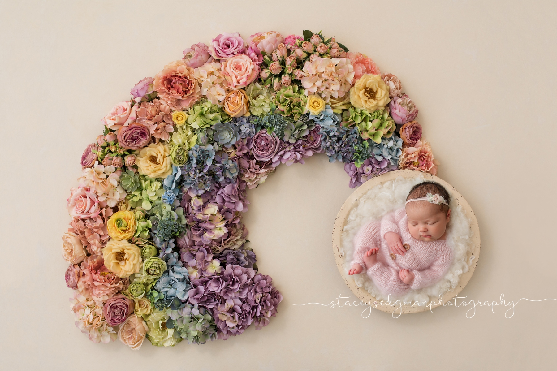 newborn girl on luisa dunn backdrop with rainbow of flowers