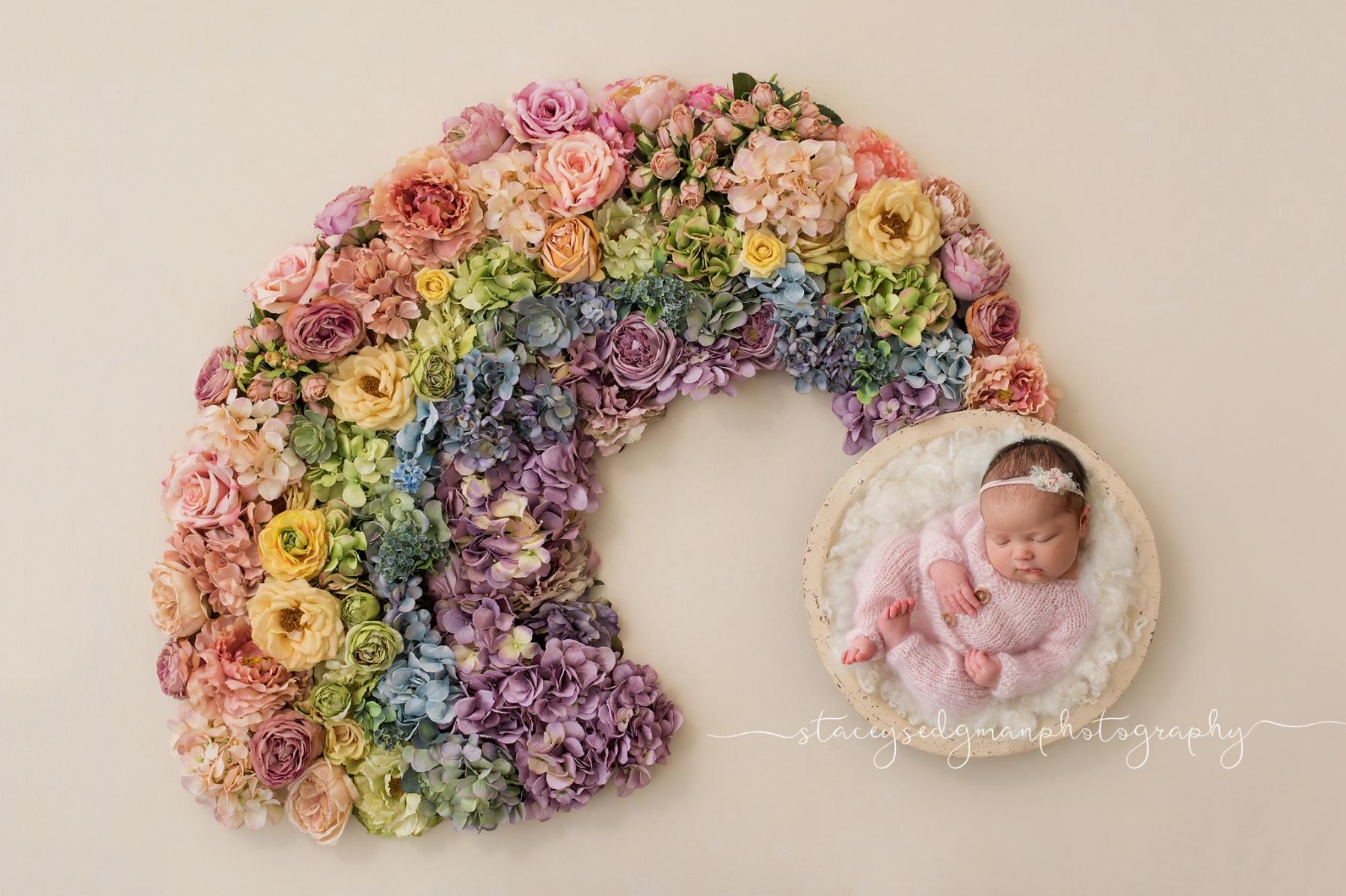 newborn girl on luisa dunn backdrop with rainbow of flowers