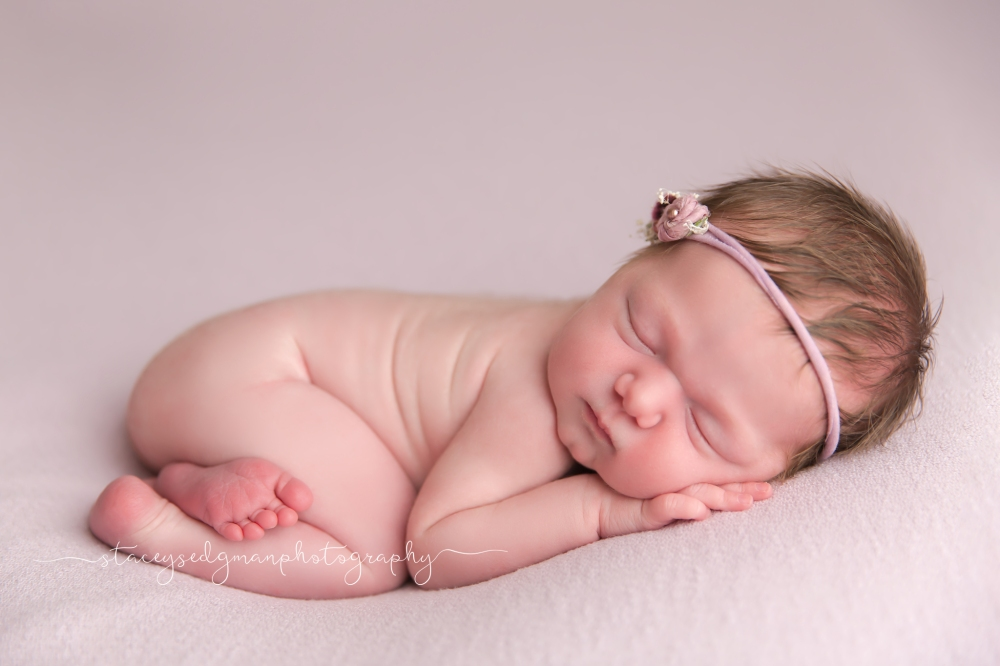 baby in a bum up pose on a shooting stars backdrop with a floral headband