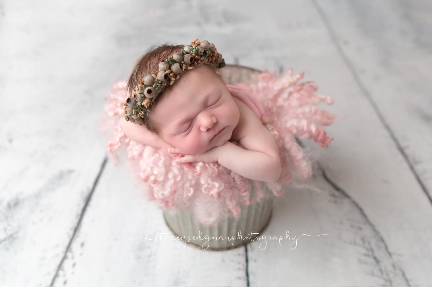 baby wearing a gumnut tie back in a bucket on a wooden backdrop