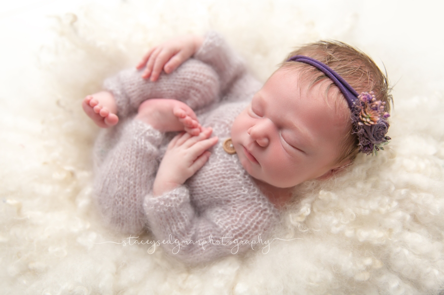 Baby in a purple knitted romper on a curly felt