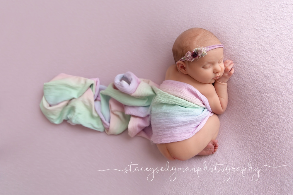 Baby in womb pose on purple backdrop wearing floral headband