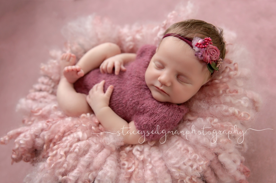 Baby in a pink knitted romper on a pink curly felt backlit by studio light
