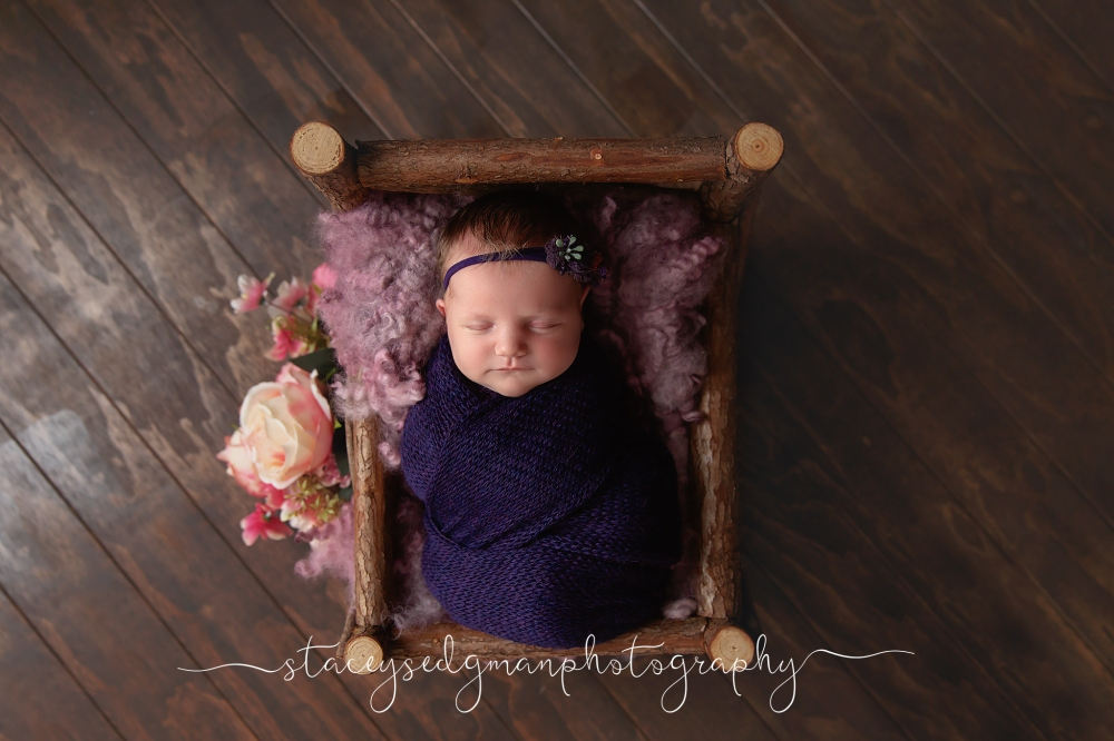 Baby wrapped in purple in a natural wooden bed