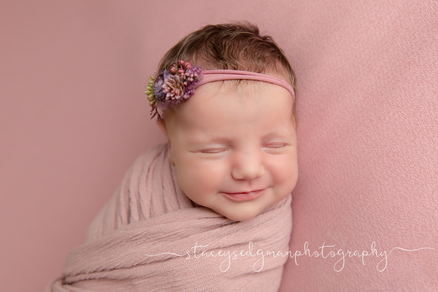 Baby girl wrapped in pink smiling