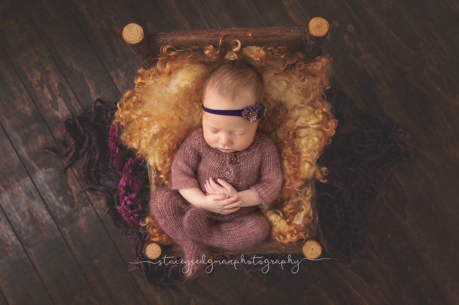 Baby in purple romper laying in wooden bed on wooden flooring