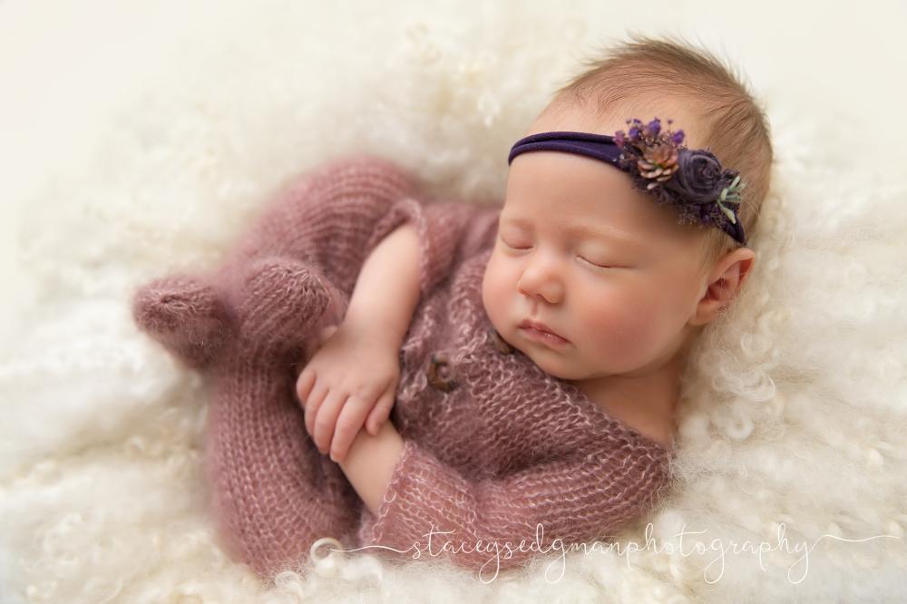 baby in purple romper wearing purple headband on cream curly felt