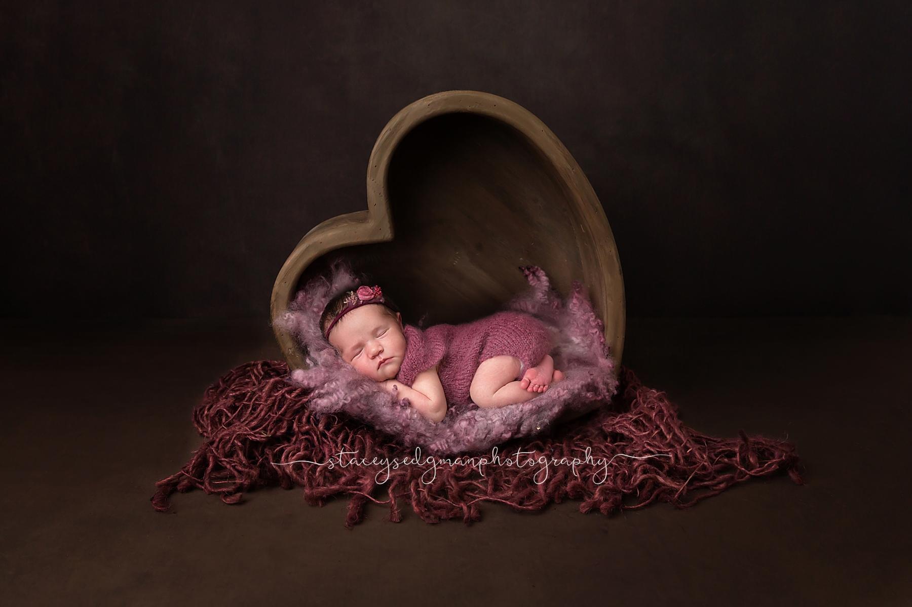 Baby in purple romper laying in wooden heart on dark backdrop