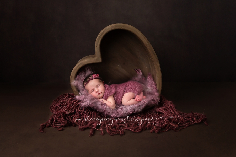 Baby in purple romper laying in wooden heart on dark backdrop